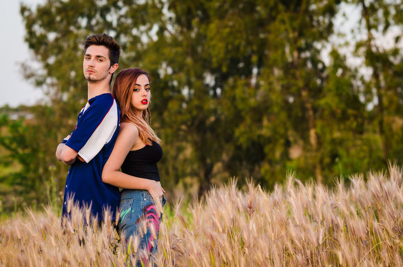 Loving Young Couple Standing On Field