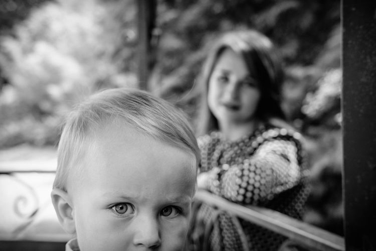 Portrait of cute boy while mother in background