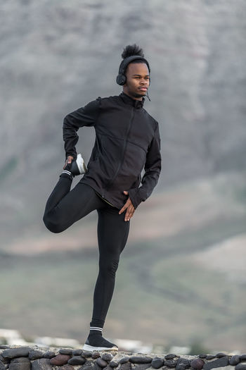 Black man doing leg exercise in countryside Man Warm Up Exercise Countryside Leg Listening Music One Person Young Adult Young Men Standing Full Length Real People Focus On Foreground Rock Day Front View Leisure Activity Lifestyles Rock - Object Solid Mountain Clothing Looking At Camera Outdoors