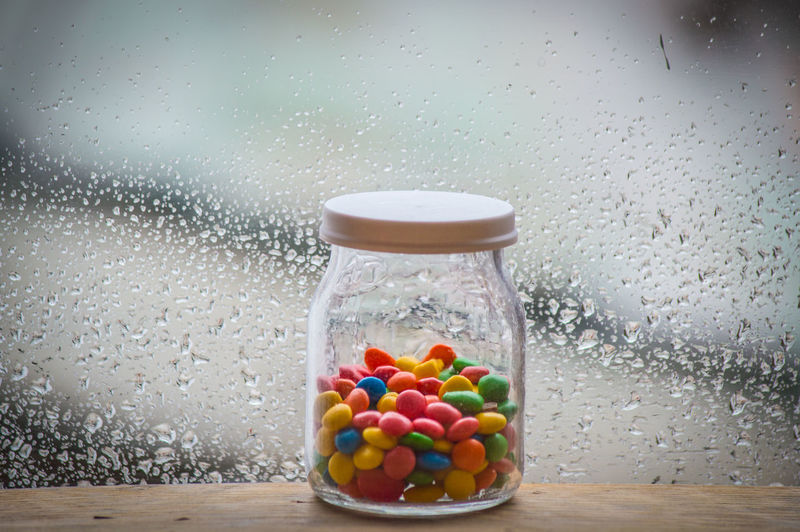 Close-up of multi colored candies in jar on table