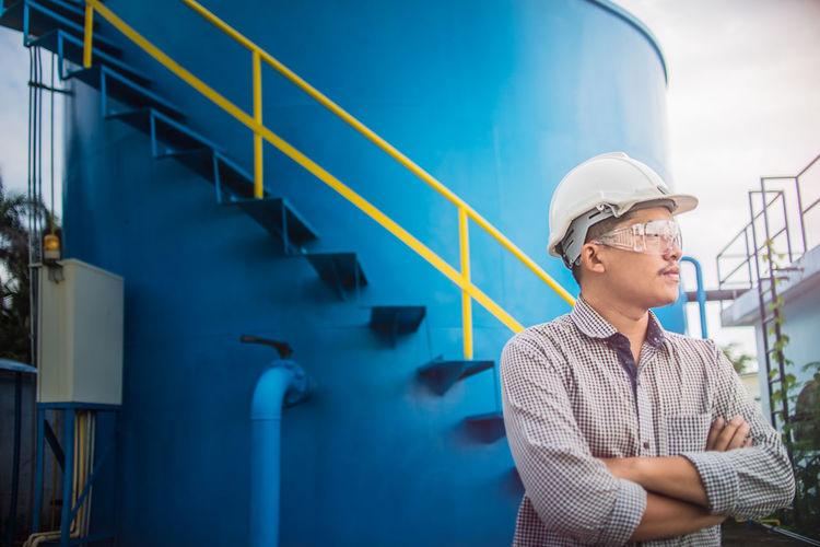 Male engineer standing against water storage tank