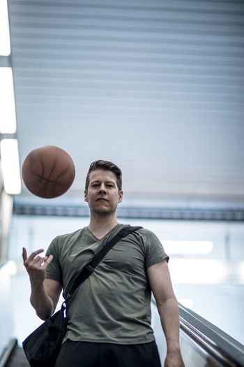 A handsome man posing for the camera while descending a subway escalator with a basketball in one hand. Adult Athletic Basketball Descending In Shape Lifestyle Man Recreation  V Neck Ball Casual Clothing Caucasian Ethnicity Escalator Handsome Model Modeling Posing For The Camera Riding Sports Sports Bag Sportswear Sporty T Shirt T-shirt Urban