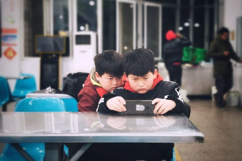 brothers PhonePhotography Wireless Technology Child Warm Clothing Technology Childhood Togetherness Portrait Boys Photography Themes Males  Self Portrait Photography Single Parent E-reader