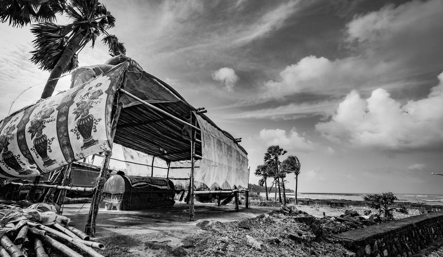 Abandoned built structure by sea against sky
