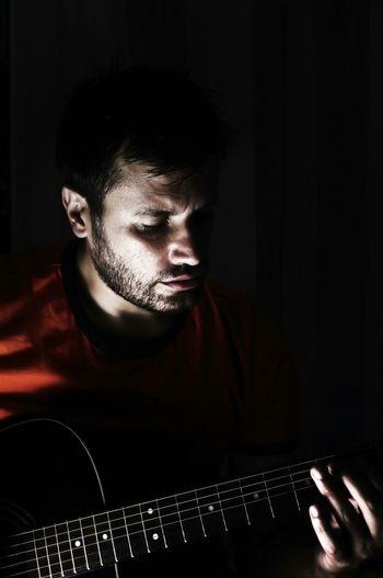 Man Playing Guitar In Darkroom