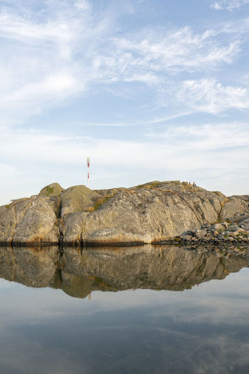 Rock formation by lake against sky