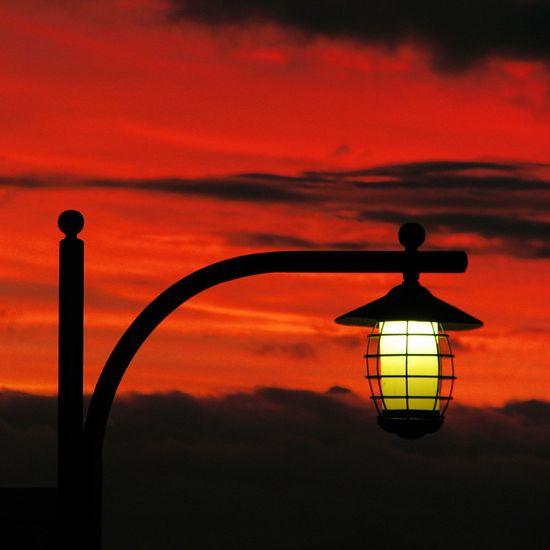 Silhouette lamp against orange sky