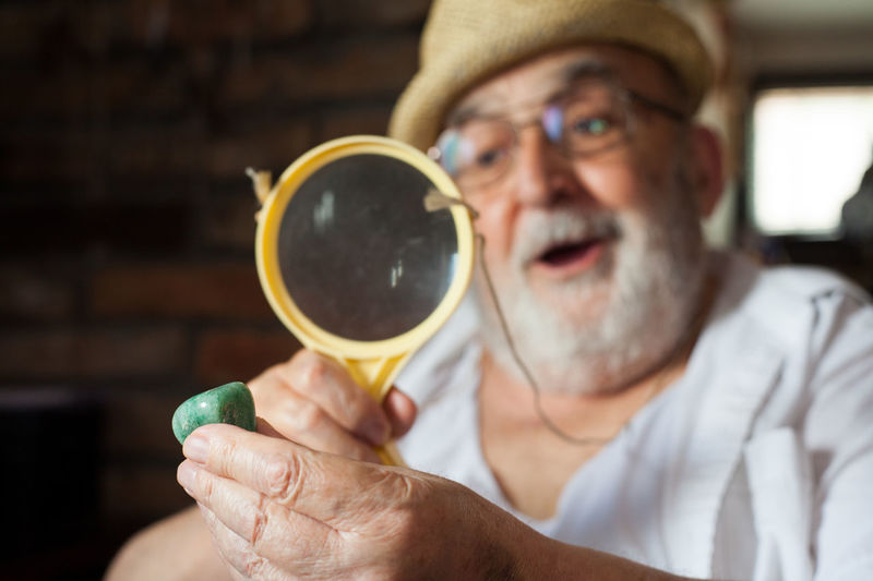 Close-up of senior man looking pebble through magnifying glass