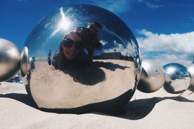 Happy man and woman at beach reflecting on metallic sphere