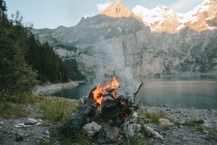 Bonfire Burning Campfire Fire - Natural Phenomenon Firewood Flame Geology Glowing Heat - Temperature Landscape Log Majestic Mountain Mountain Range Non-urban Scene Outdoors Physical Geography Smoke - Physical Structure Tourism Tranquil Scene Tranquility Travel Destinations Vacations Valley Water
