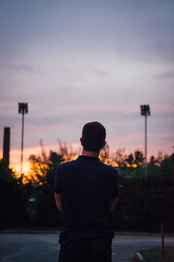 Rear view of man standing on street against sky during sunset