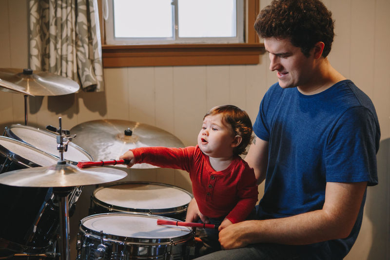 Cute boy playing drum while sitting with father at home