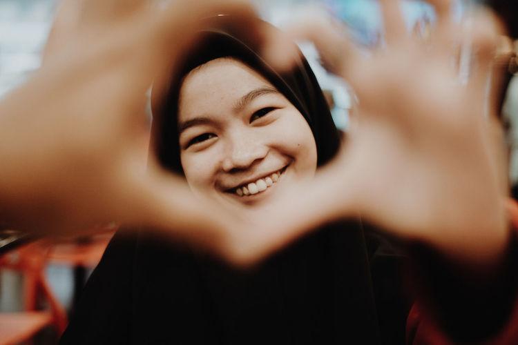 Portrait of smiling teenage girl seen through heart shape