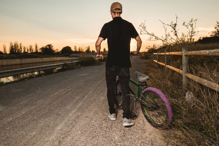 Portrait of man standing by bicycle against sky during sunset
