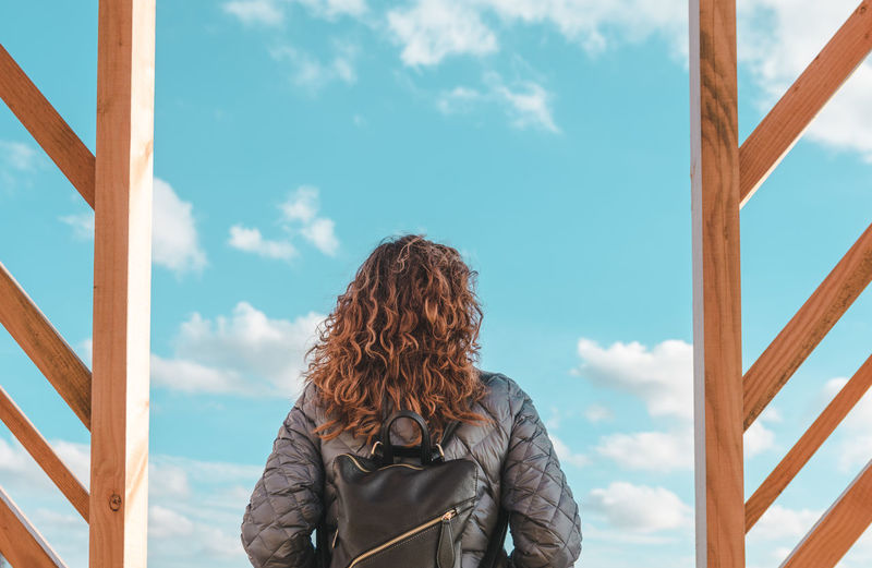 Rear view of mature woman with backpack standing against blue sky