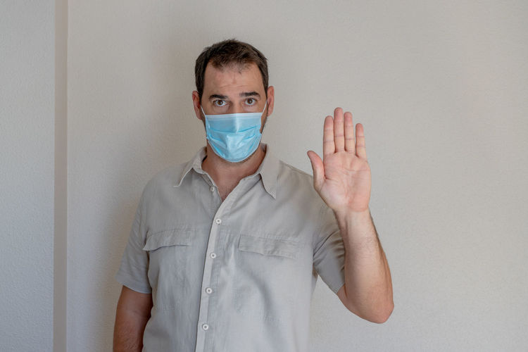 Portrait of man wearing flu mask gesturing while standing against white wall