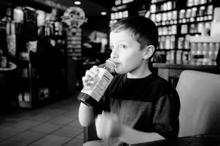 "Starbucks - Grand Island Nebraska ""I don't like this place Dad"" - Victor A Day In The Life Bottle Candid Portraits Childhood Close-up Consumerism Contemplation Drinks Focus On Foreground Front View Holding Indoors  Innocence Juice Monochrome One Person Selective Focus Sitting Starbucks"