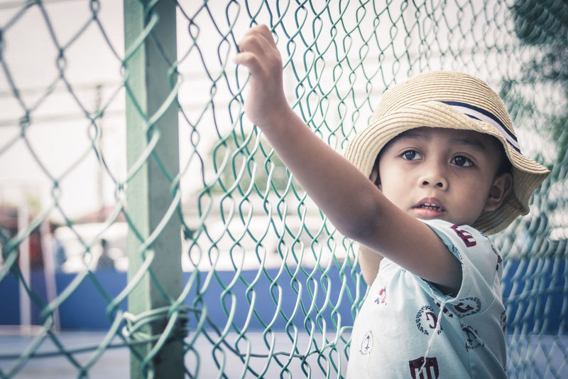 One fine day Chainlink Fence Child Childhood Children Only One Person Protection Standing People Outdoors Day Real People Human Hand The Portraitist - 2017 EyeEm Awards Young Adult Boy Lifestyles Portrait Children Children Of The World Children's Portraits Face Expression EyeEmNewHere The Portraitist - 2018 EyeEm Awards