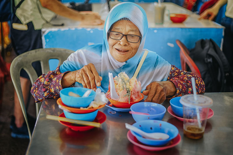 Malaysian female senior citizen enjoying her delicious dishes Air Batu Campur Food And Drink Real People Front View Food Table One Person Business Indoors  Holding Women Men Lifestyles Eyeglasses  Freshness Spoon Occupation Kitchen Utensil Adult Preparation  Temptation Old Women Old Citizen
