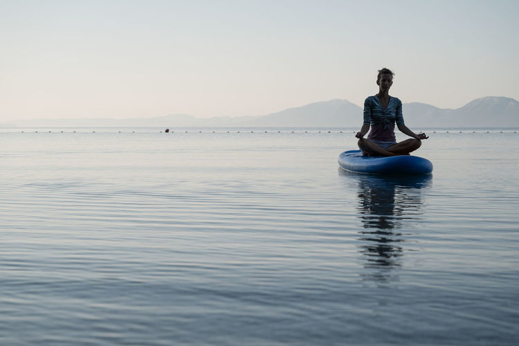 Man sitting in water against clear sky
