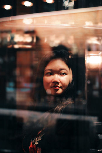 Young Woman Looking Away Seen Through Glass