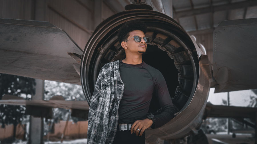 Young man wearing sunglasses standing at aircraft hangar