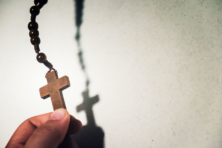 Cropped Hand Of Person Holding Rosary Against Wall