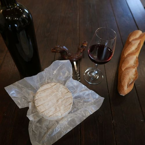 High Angle View Of Camembert And Baguette With Wine On Wooden Table