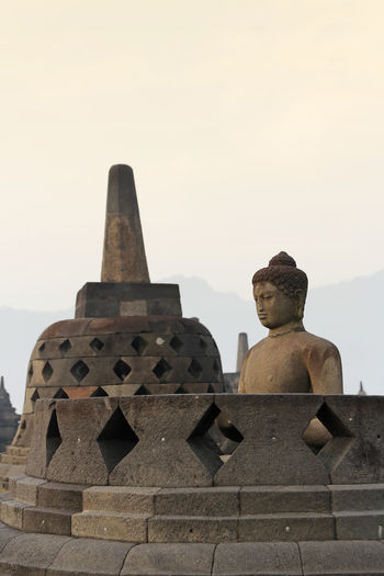 Borobudur Temple with the Buddha statue during sunrise, Yogyakarta, Indonesia Yogyakarta Ancient Civilization Architecture Art And Craft Belief Borobudur Buddhism Built Structure Creativity Day History Human Representation Male Likeness No People Place Of Worship Religion Representation Sculpture Sky Spirituality Statue Stone Material