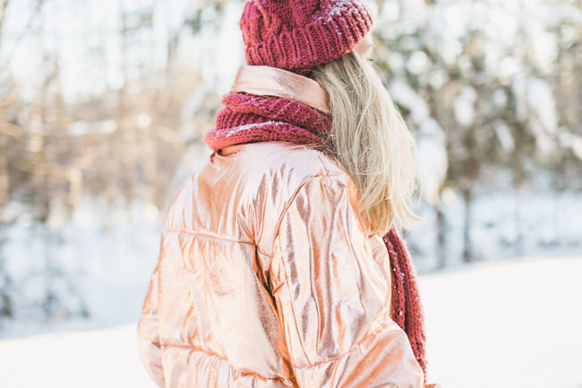 Beautiful blonde woman wearing a fashionable bronze winter jacket, red scarf, hat and mittens on a sunny day in a cold winter forest. Alone Blonde Bright Bronze Golden Winter Fashion Beanie Beautiful Woman Caucasian Cold Temperature Day Forest Leisure Activity Lifestyles Outdoors Pretty Red Light Sunny Day Warm Clothing Warmth Winter Winter Wonderland