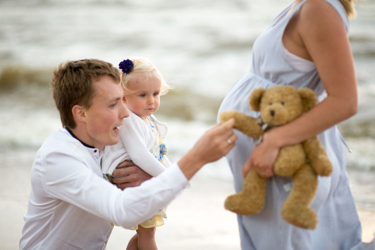 Man With Daughter And Woman At Beach