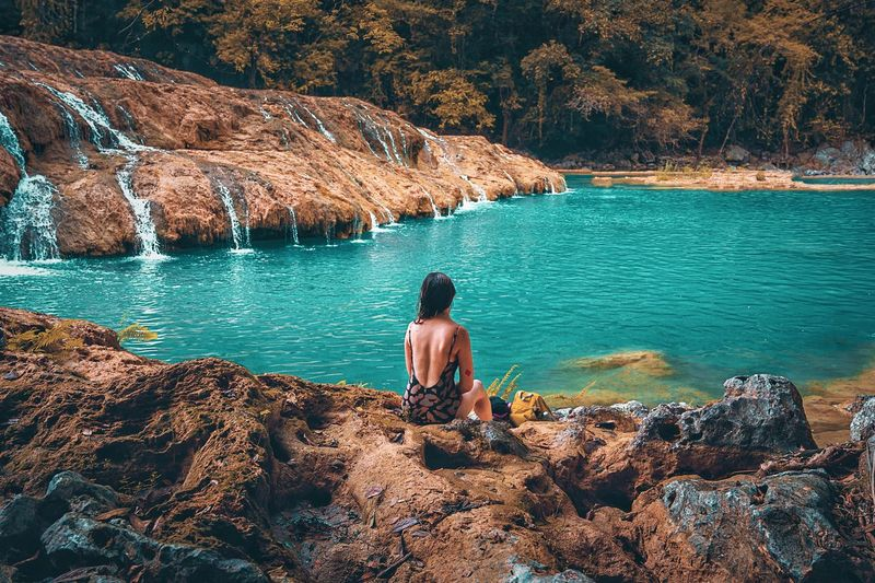 Rear view of woman sitting on rock by semuc champey lake in guatemala