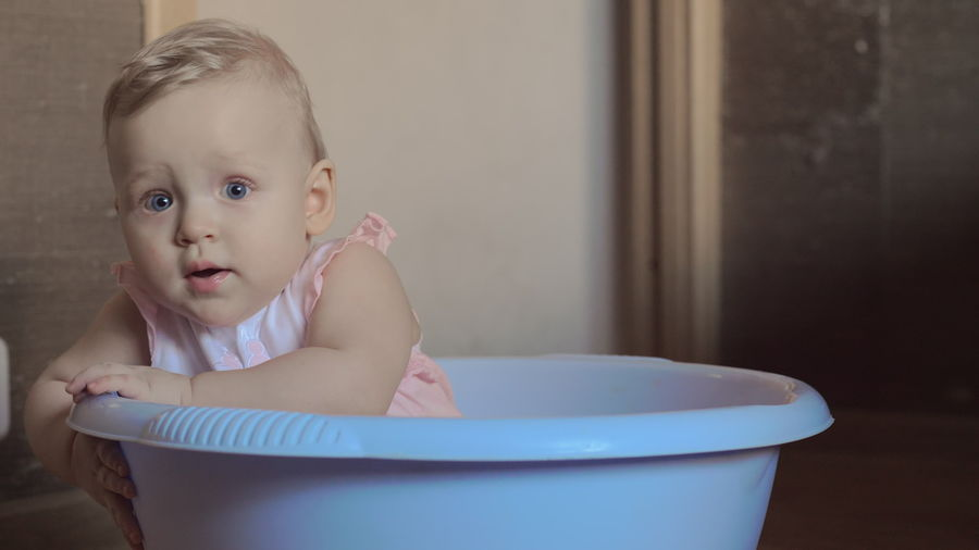 Portrait of cute baby girl in bathroom