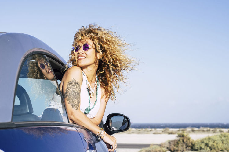 Beautiful cheerful happy caucasian woman outside the car with wind in curly long blonde hair - attractive people enjoying the freedom in outdoor coastline ocean vacation place Mode Of Transportation Transportation Car Young Adult Motor Vehicle One Person Sky Portrait Adult Hairstyle Leisure Activity Beautiful Woman Nature Hair Beauty Day Land Vehicle Happiness Smiling Fashion Outdoors Road Trip Blue Curly Hair Enjoying Life Happiness One Woman Only Caucasian Hippie Tattoo Freedom Horizon Over Water Sea Seascape People Mother Daughter Beach Journey Vacations Females 40-44 Years Tropical Climate Coastline