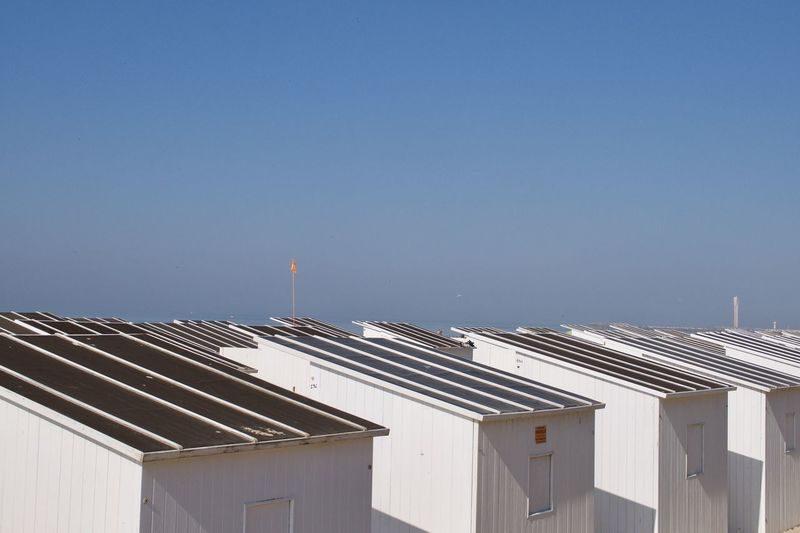 High angle view of beach huts against clear blue sky