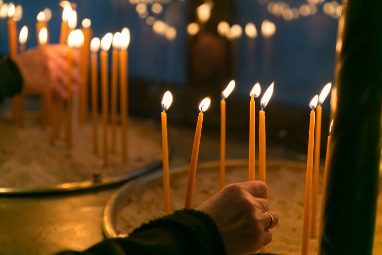 Human hand holding lit candles against temple