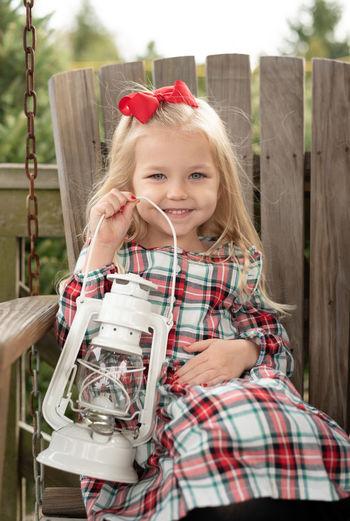 Portrait of cute smiling girl holding lantern sitting on swing