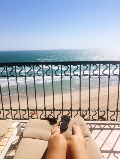 Low section of woman relaxing by railing at beach against clear sky