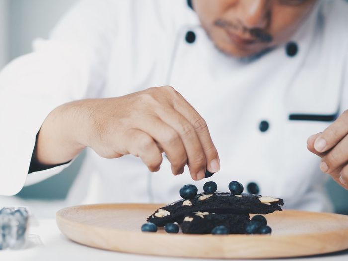 Midsection of chef garnishing berries on sweet food