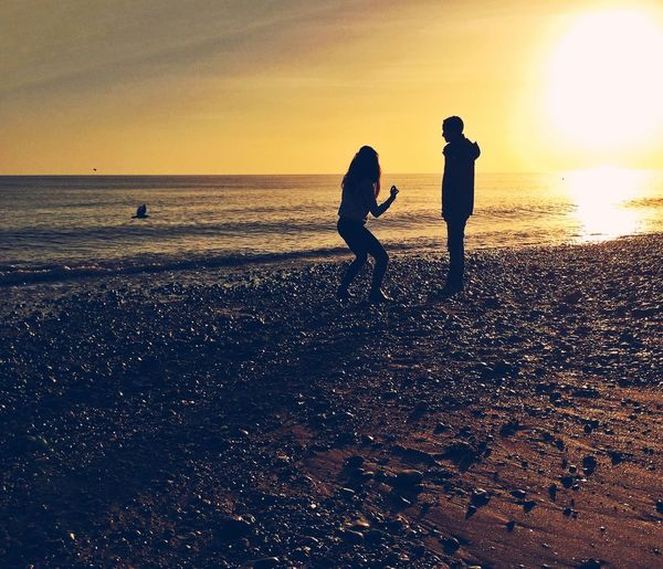 Silhouette Of Couple On Beach During Sunset