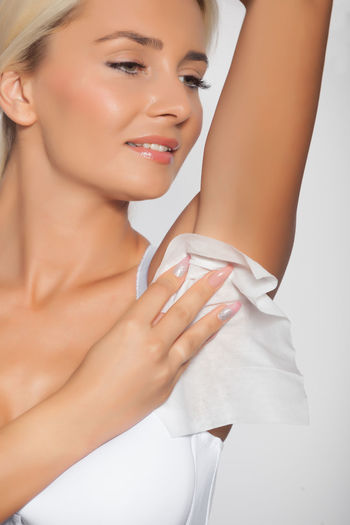 Smiling young woman cleaning armpit with tissue paper against white background