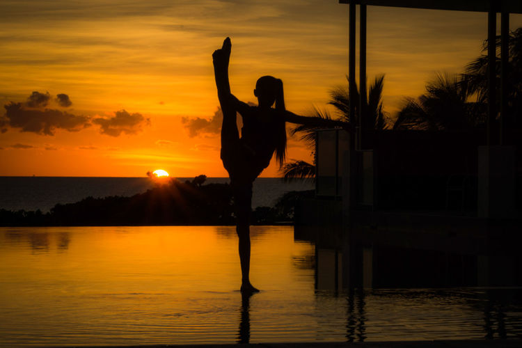 Silhouette woman with arms raised against orange sunset sky