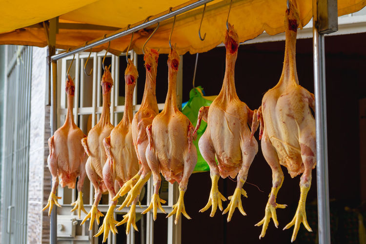 Chicken meat hanging at market stall for sale
