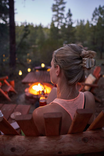 Rear view of young woman sitting by fire pit at dusk