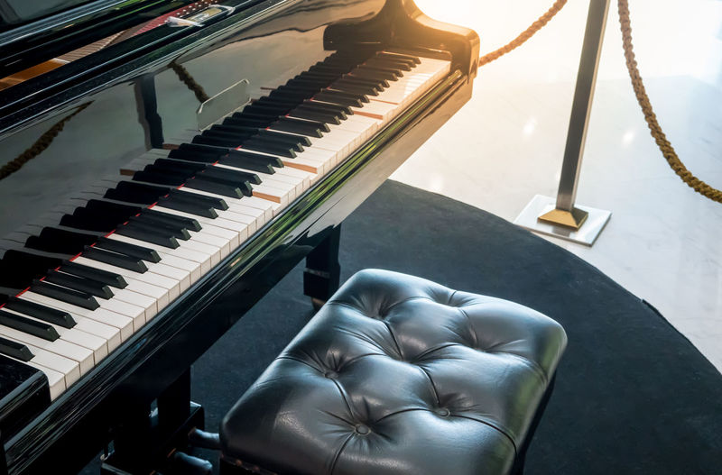 Auto Play Piano keys side view and black leather chair with shallow depth of field Modern Music Arts Culture And Entertainment Automatic Classical Music Close-up Day Decoration Flare Grand Piano High Angle View Indoors  Interior Light And Shadow Music Musical Instrument No People Piano Piano Key Songs
