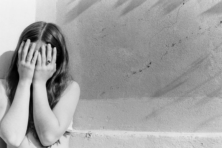 Woman with hands covering face standing against wall