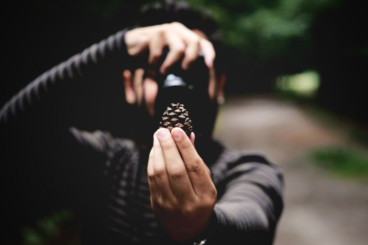 Young man photographing pine cone while standing outdoors