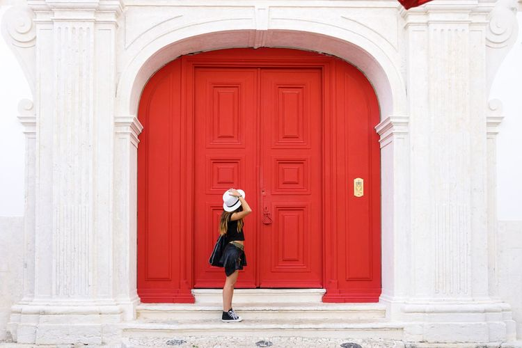 Side view of woman standing by closed red door