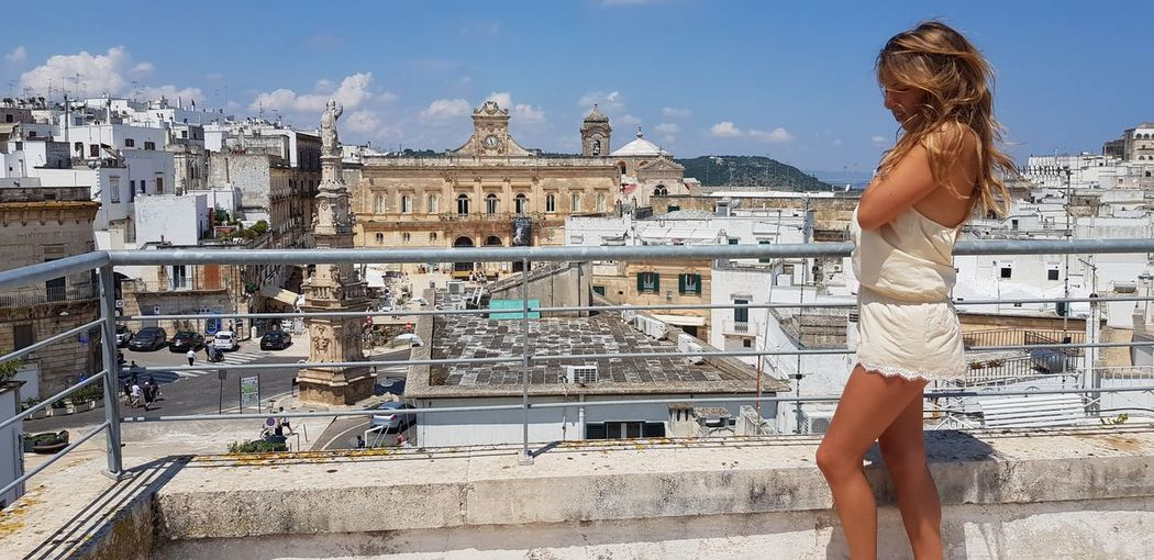 Side View Of Woman Standing On Building Terrace During Sunny Day