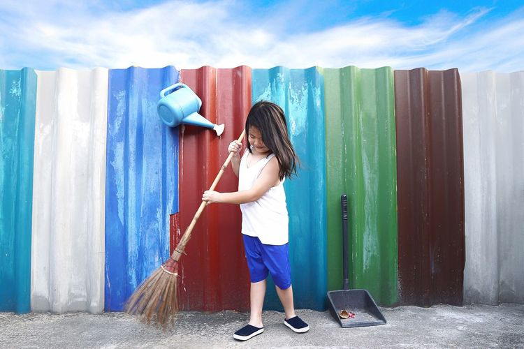 Asian little cute girl sweeping the floor with broom at outdoor on colourful wall and blue sky kid doing household cleaning and housekeeping concept. Casual Clothing Child Childhood Cleaning Day Females Full Length Girls Hairstyle Holding Innocence Leisure Activity Lifestyles One Person Outdoors Real People Standing Wall - Building Feature Women Young Adult